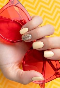 最小限のスタイルでトレンディな黄色のマニキュアで手入れの行き届いた女性の手。