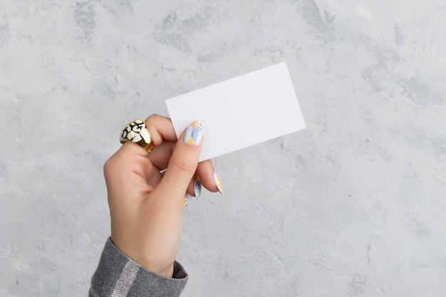手入れの行き届いた女性の手は灰色のコンクリートの背景にポストカードを持っています。プレーンなコールカードのモックアップテンプレート。