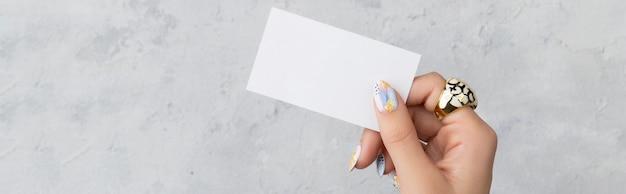 コンクリートの灰色の背景にポストカードを持っている手入れの行き届いた女性の手