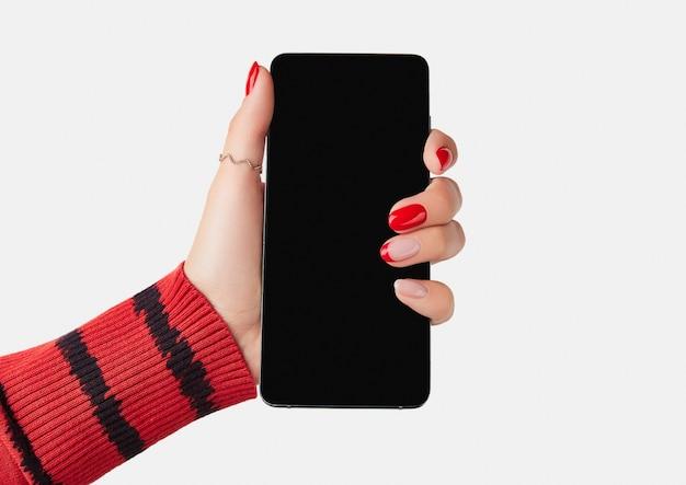 空白の画面でスマートフォンを持っている手入れの行き届いた女性の手