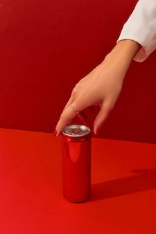 Manicured womans hand with soda can on a red background in sunlight