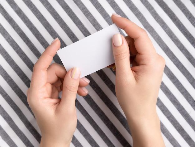 空白のカードを保持している手入れの行き届いた女性の手。フラットレイ、ホームオフィス教育コンセプトでのトップビュー作業。