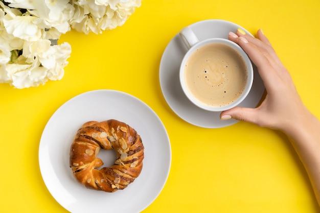 手入れの行き届いた女性の手は黄色の背景にコーヒーのカップを保持しています。フラットレイ、トップビュー春夏朝食発売ブランチコンセプト。