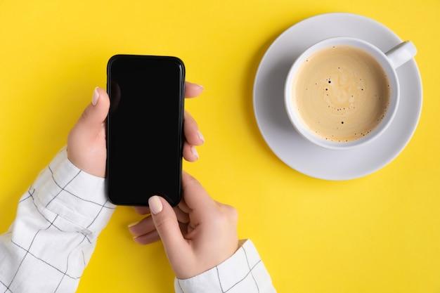 잘 손질 된여 대 손 빈 화면으로 스마트 폰 들고. 홈 오피스 교육 개념에서 평면 위치, 최고보기 작업.
