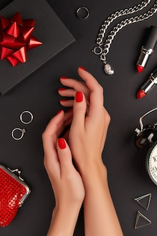 Manicured womans hands with accessories on black background halloween manicure pedicure design trends