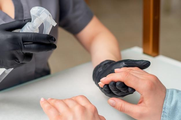 Маникюрша наносит спрей на руки клиентов.