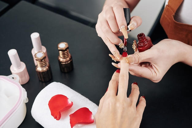 Мастера маникюра, применяя лак для ногтей