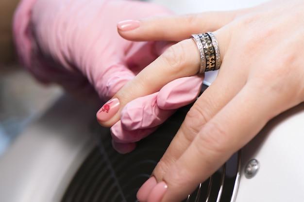 Маникюрша делает дизайн ногтей гель для клиента, крупным планом.