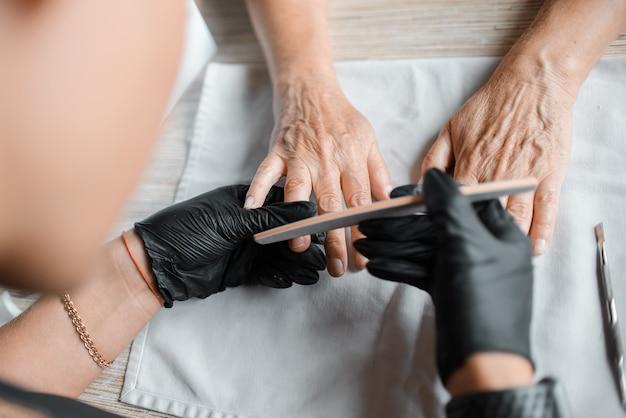 Мастер маникюра подпиливает ногти пожилой женщины, вид сверху