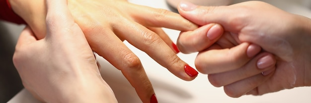 Manicurist gives the client a hand massage with oil