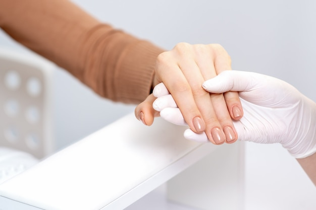 Рука мастера маникюра держит руку женщины с бежевым маникюром крупным планом.