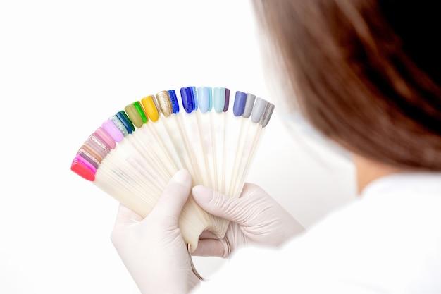 Руки мастера маникюра держат палитру образцов цвета ногтей маникюра
