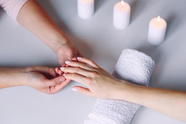 매니 큐 어사 손을 여성 고객의 손에 마사지를 하 고 있습니다.