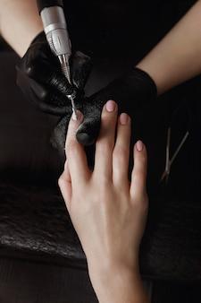 Мастер маникюра в черных перчатках, шлифовальный станок снимает старый гель-лак. подготавливает к наращиванию ногтей. спа-услуги. маникюрный кабинет.