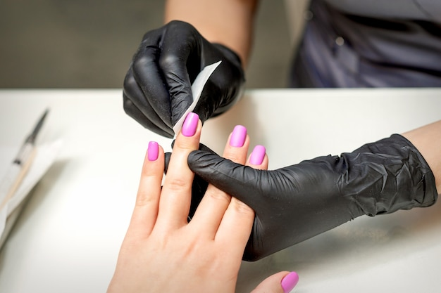 Manicurist is cleaning pink nail polish on female fingernails after manicure procedure in nail salon