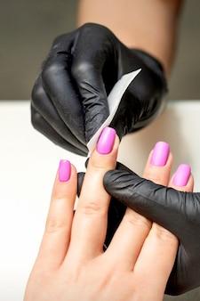 Мастер маникюра чистит розовый лак на женских ногтях после процедуры маникюра в маникюрном салоне