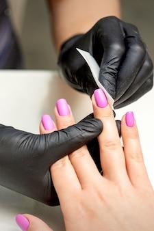 ネイリストはネイルサロンで女性の指の爪のピンクのマニキュアを掃除しています