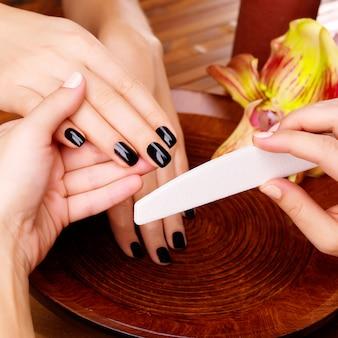 ネイリストマスターが女性の手でマニキュアを作る-スパトリートメントのコンセプト