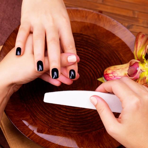 Il maestro del manicure fa la manicure sulle mani della donna - concetto di trattamento termale