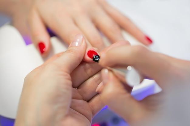 Мастер маникюра делает красный маникюр на руке молодой женщины. мастер маникюра женщина делает ногти клиентке девушки в салоне красоты. уход за руками