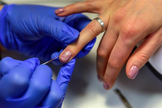 ネイリストが女性のクライアントに爪を塗るクローズアップ。美容師が爪にアートデザインをしています。ビューティーサロンでのプロの手とネイルケア