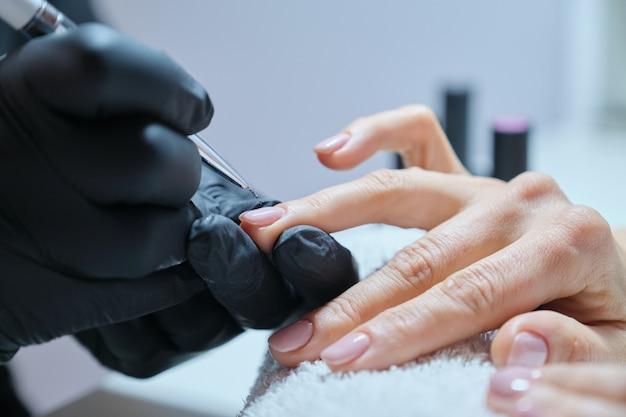 ネイリストが女性のクライアントにネイルを塗る