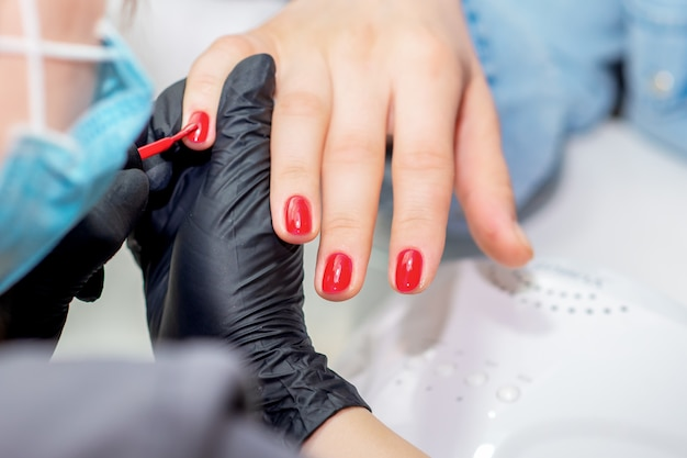 Мастер маникюра красит ногти.