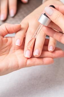 Маникюрша наливает масло на ногти женщины