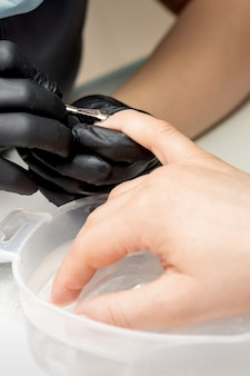 Manicurist removing cuticle from female nails by metal pusher during soaking fingernails in the bath at nail salon