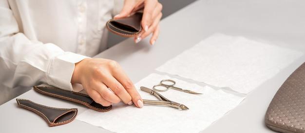 Руки мастера по маникюру кладут инструменты для маникюра на стол, готовясь к процедурам маникюра
