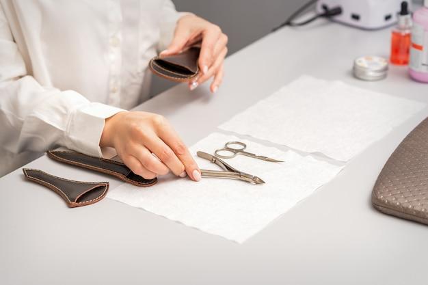 ネイリストの手がマニキュアツールをテーブルに置き、マニキュア手順の準備をします