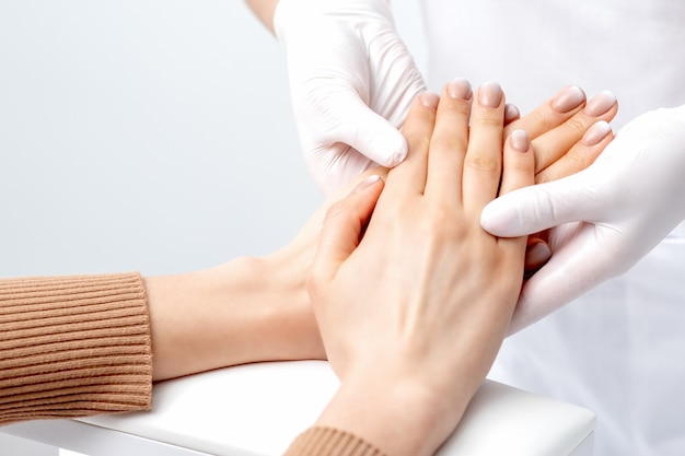 ネイルサロンでマニキュアと女性の手にワックスマッサージをしている手袋を着用しているネイリスト