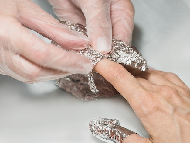 Manicurist wrapping finger nails with foil during the procedure of manicure
