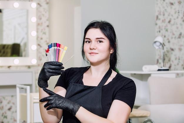 美容院の手に笑顔とプロのツールを持つネイリストの若い美しい女性