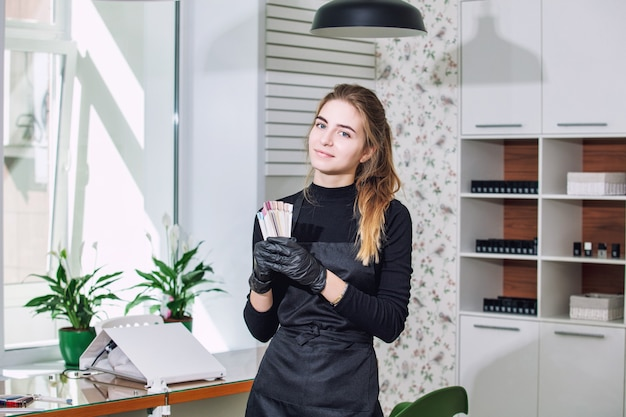 Маникюрша молодая красивая женщина с улыбкой и профессиональными инструментами в руках салона красоты