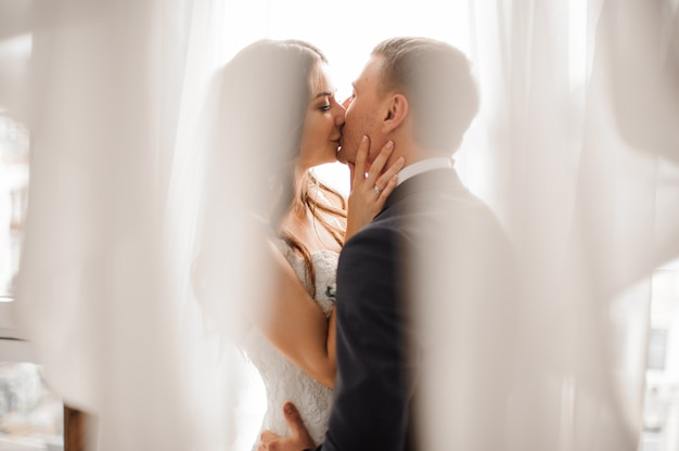 Manly groom and beautiful bride kissing against white scene