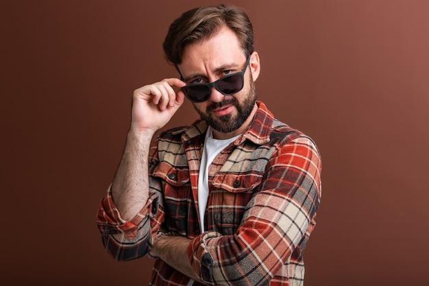 Uomo barbuto alla moda bello hipster virile su colore marrone