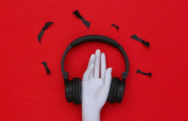 빨간색 배경에 박쥐가 있는 마네킹 손과 스테레오 헤드폰
