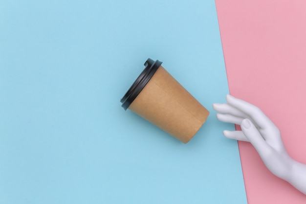 Mannequin hand and cardboard coffee cup on blue pink pastel background. top view