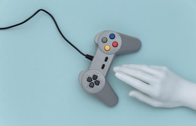 Рука манекена касаясь ретро геймпада на синем фоне. вид сверху. креативное искусство, минимализм