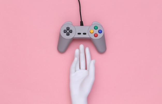 Рука манекена касаясь ретро геймпада на розовом фоне. вид сверху. креативное искусство, минимализм