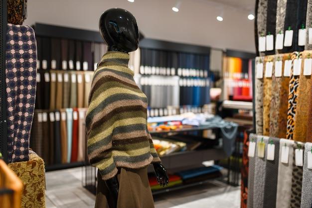Манекен в куртке в текстильном магазине, никто. витрина с тканью для шитья