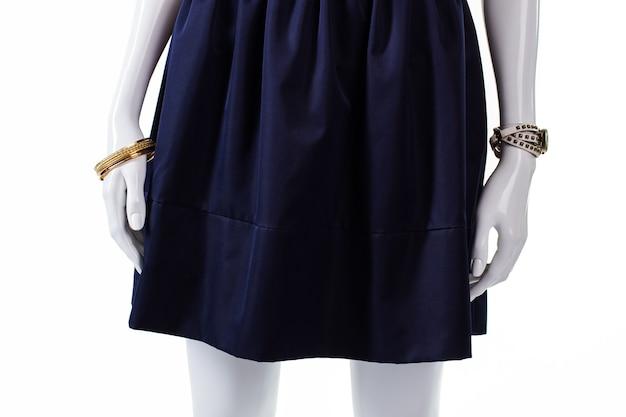 블루 네이비 스커트의 마네킹. 주름이 있는 네이비 코튼 스커트. 스커트가 있는 여성용 손목 액세서리. 어두운 새 옷.