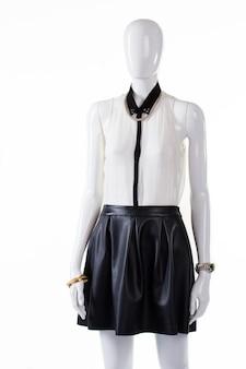 블라우스와 스커트를 입은 마네킹. 블라우스가 달린 여성용 가죽 스커트. 주름이 있는 블라우스와 스커트. 쇼케이스에 있는 고급 여름 복장.