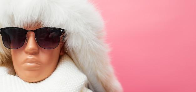 Манекен с очками и шарфом, скидки на зимнюю одежду и аксессуары, на розовом фоне