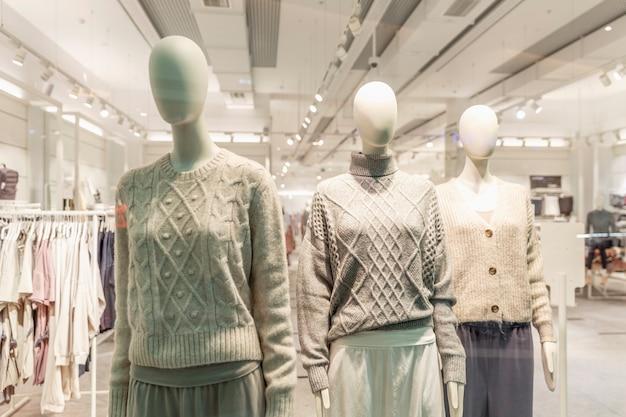 Манекены в витрине магазина одежды. демонстрация новой коллекции.