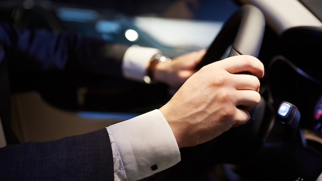 자동차를 운전하는 동안 스티어링 휠에 큰 손을 댄다.