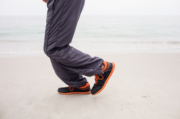 Mans foot while jogging on the beach