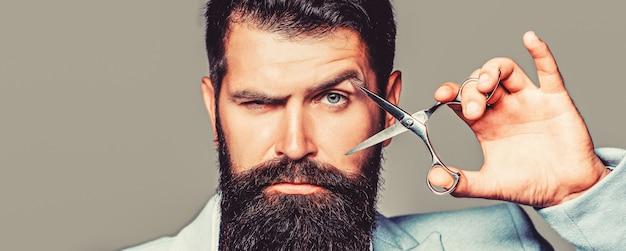 理髪店でマンヘアカット。理髪はさみ、理髪店。残忍な男、口ひげ。理髪店の男性、散髪、シェービング。灰色の背景に分離されたひげを生やした男