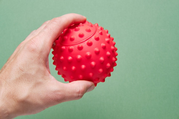 In a mans hand a ball for working out trigger points or a physiotherapy ball for reflexology